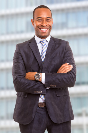 Young handsome african business man posing in front of a modern building photo