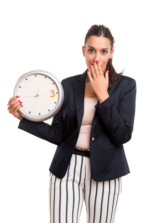 llegar tarde: Joven mujer de negocios, que parece llegar tarde, mirando el reloj