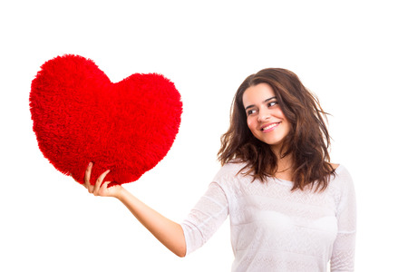 Young woman with a heart pillow in her hands - Valentines day concept photo