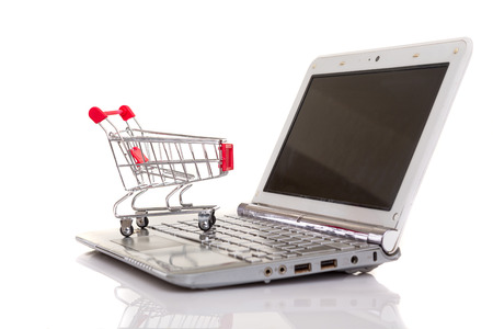Studio shot of a  shopping cart over a laptop computer