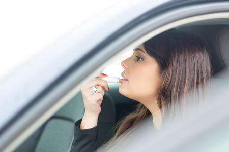 stopped: Business woman retouching her makeup while stopped in the traffic Stock Photo