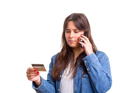 Woman placing an order at the phone with her credit card photo