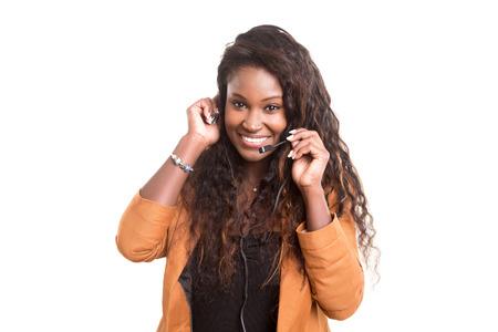 servicio al cliente: Un operador de teléfono amistosa africano sonriente aislados sobre un fondo blanco Foto de archivo