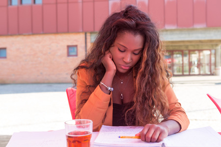 exam: Young african student preparing her exams at a local cafeteria