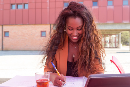 african student: Young african student preparing her exams at a local cafeteria