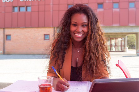 pretty black woman: Young african student preparing her exams at a local cafeteria