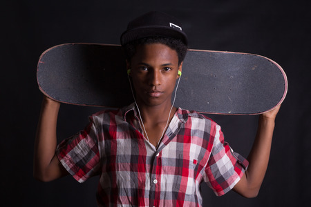 teenage male: A young black skater posing in studio