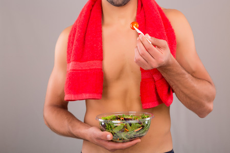 toallas: Hombre apto sosteniendo un plato de ensalada fresca después de un día de entrenamiento Foto de archivo