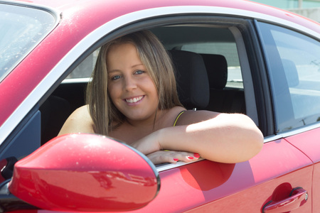 Beautiful large woman driving a red sports car photo