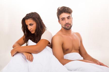 sexo pareja joven: Pareja joven deprimida en la cama - problemas Daylife concepto