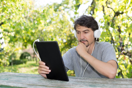 Young man relaxing with a tablet computer at a garden photo