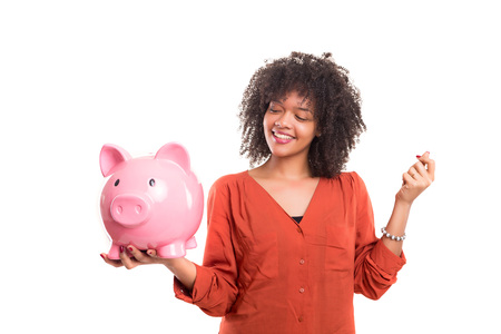 white fund: African woman putting some money into a piggy bank
