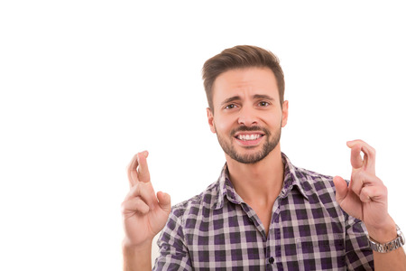 crossed fingers: Man with crossed fingers, isolated over a white background Stock Photo