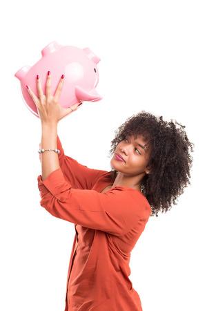 banco dinero: mujer africana tratando de conseguir algo de dinero de una alcancía Foto de archivo