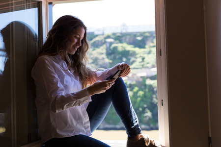 some: Young woman catching some sun at the balcony while using her new smartphone Stock Photo