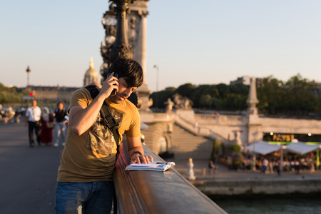 Young man on vacations in Paris, relaxing over the Alexander the 3rd bridge photo