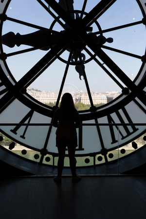 Clock at the Musee DOrsay in Paris France. In the back we see the Sacre Coeur Basilica in Montmatre