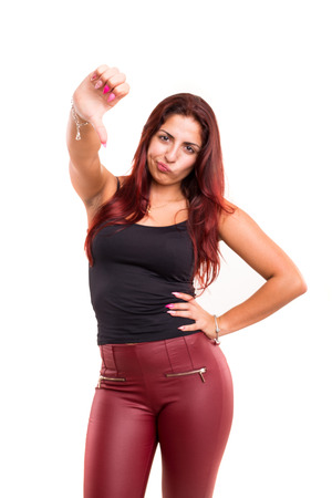 Studio shot of a young woman signaling thumbs down