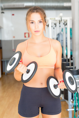 Young woman getting into shape at the gym