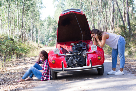 hassle: Friends on a roadtrip having a problem with their old car