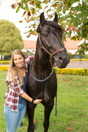 Beautiful and natural young woman spending sometime with her horse Stock Photo