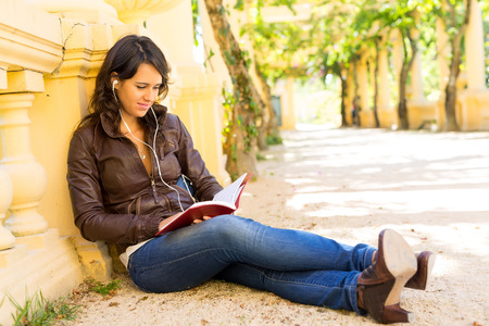 Young woman reading a book and relaxing at the park photo
