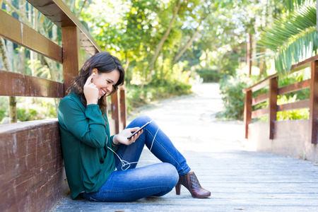 Young woman listening to music at the park photo