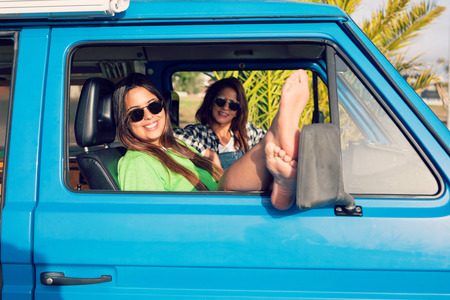 Summer holidays, road trip, vacation, travel and people concept - smiling young hippie women in car