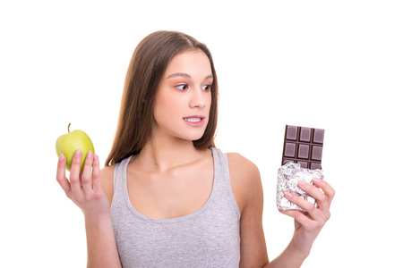 Thoughtful young blonde woman hesitating between a fruit and chocolate, isolated over white background Stock Photo