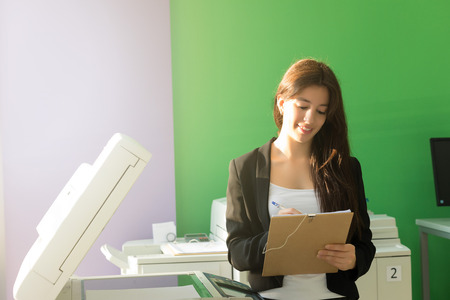 A young student at a copy center taking some copies for her final exams