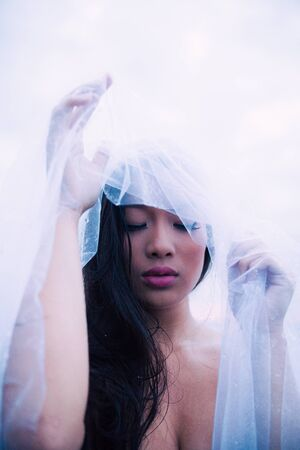 Asian model with bridal veil in the water enjoying a wellness spa.