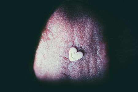 Heart shaped pil on tongue in macro close-up.