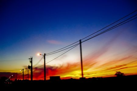view of sunset while roading with electric telephone pole Stock Photo