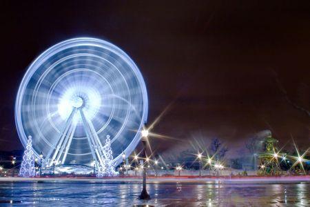 spinning fair wheel at night in paris Stock Photo
