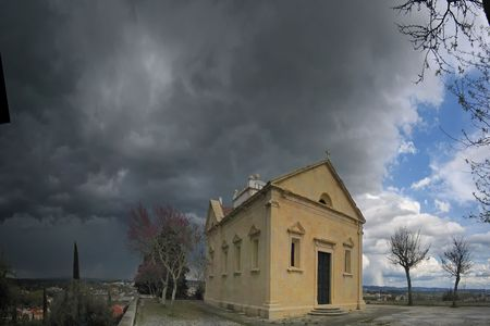 small isolated chapel with a aproaching storm in the background