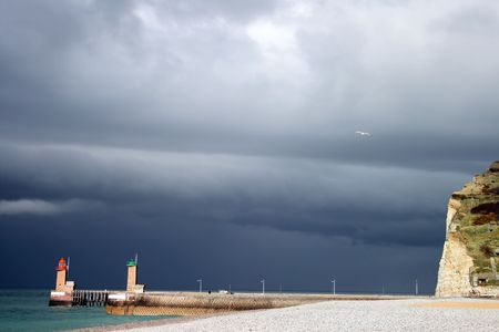 people walking in normandys Fecamp harbour in a stormy day