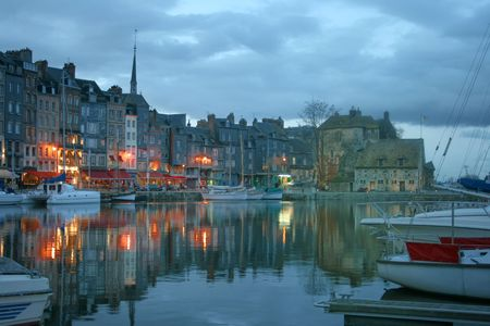 view of the old ports of honfleur (normandy, france) at dusk with the historic buildings illuminated