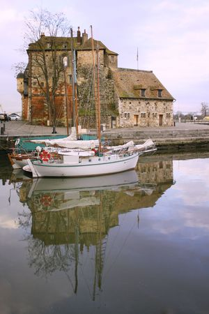 view of the old capitainerie in the vieux bassin in Normandys Honfleur , France with sailing boats docked