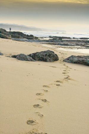 footsteps in sandy beach towards horizon Stock Photo