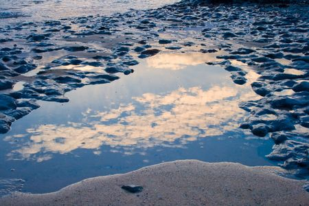 sky reflection in a small pond in a rocky beach Stock Photo - 6252371