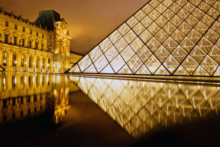 museum visit: night view of the louvre palais courtyard with reflection