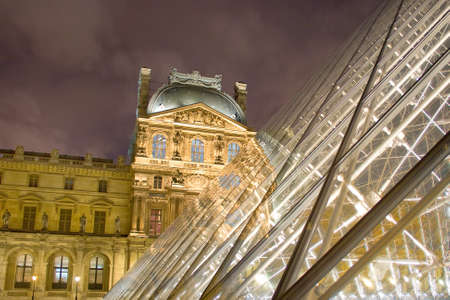 night view of louvre museum with glass pyramid int the foreground