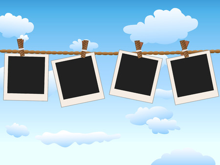 4 Blank photo frames hanging on the rope in blue sky