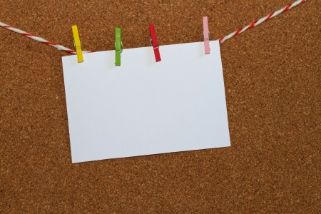 Blank note paper hangs on the wooden board