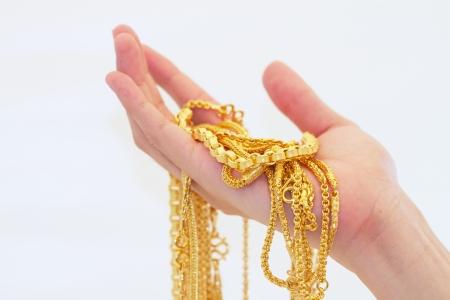 金: 金のネックレスを持っている手 写真素材