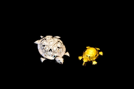 Silver with diamond turtle and golden turtle on black background Stock Photo - 17242640