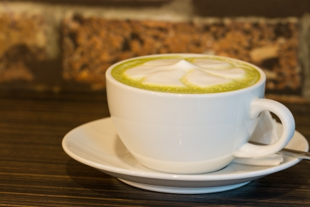 A cup of green tea latte on wooden table