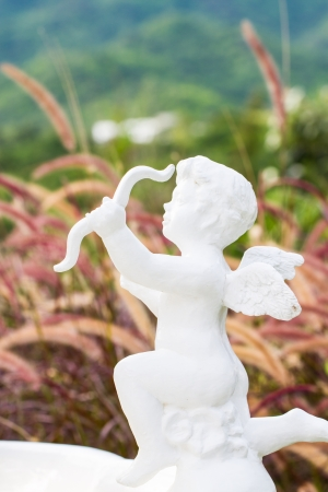 Little cupid sculpture among nature Stock Photo