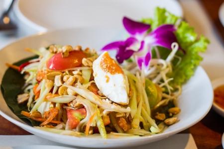 thai style papaya salad with salty egg photo