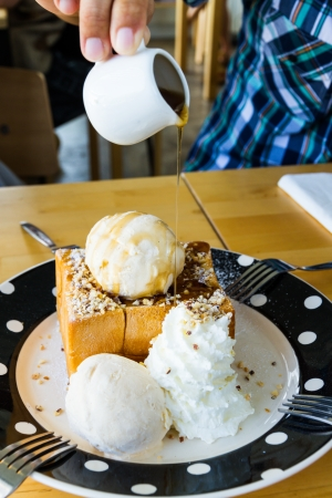 man pouring honey syrup on almond honey toast photo